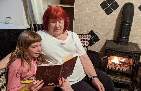 Foto eines 8 jährigen blonden Mädchens das seiner Oma das Buch Die bunte Märchentraube vorliest